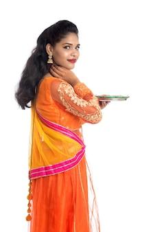Ritratto di una ragazza tradizionale indiana che tiene diya, ragazza che celebra diwali o deepavali con la lampada a olio della holding