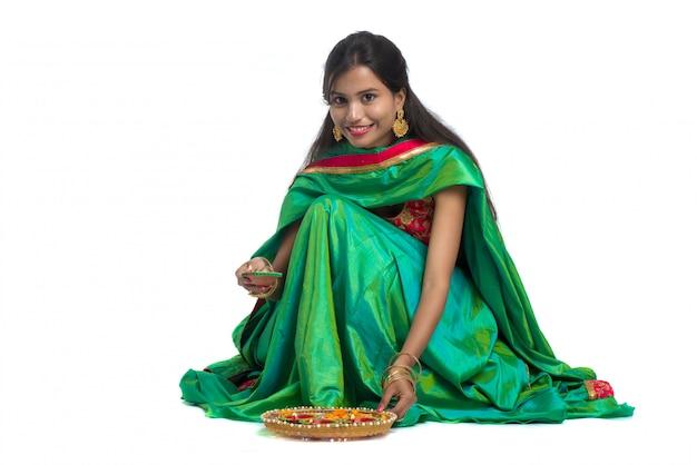 Ritratto di una ragazza tradizionale indiana che tiene diya e che produce rangoli. ragazza che celebra diwali o deepavali con la lampada a olio della tenuta durante il festival di luce su fondo bianco
