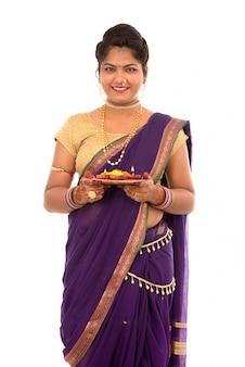 Ritratto di una ragazza tradizionale indiana che tiene il thali di pooja con il diya durante il festival di luce su fondo bianco. diwali o deepavali
