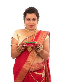 Ritratto di una ragazza tradizionale indiana che tiene pooja thali con diya durante la festa della luce su uno spazio bianco. diwali o deepavali