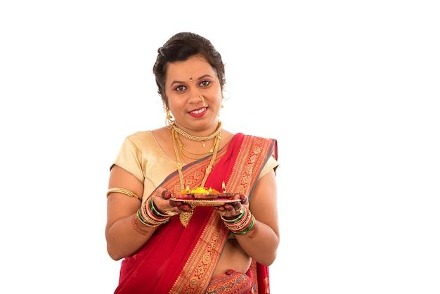 Ritratto di una ragazza tradizionale indiana che tiene pooja thali con diya durante la festa della luce su bianco