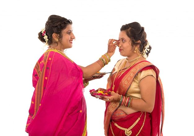 Ritratto di ragazze tradizionali indiane holding diya e fiore thali, sorelle che celebrano il diwali o deepavali holding lampada a olio durante il festival su uno spazio bianco