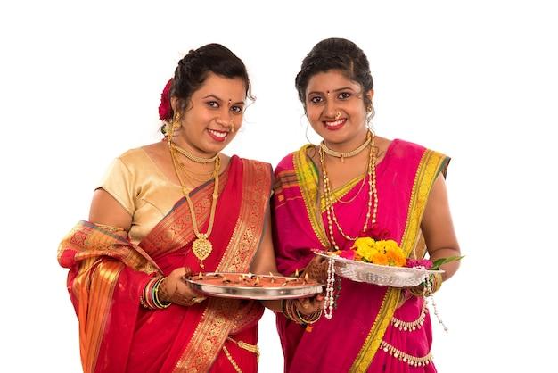 Ritratto delle ragazze tradizionali indiane che tengono diya e thali del fiore