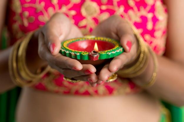 Ritratto di una donna indiana tradizionale che tiene diya, donna che celebra diwali o deepavali con tenendo la lampada a olio durante la festa della luce su bianco
