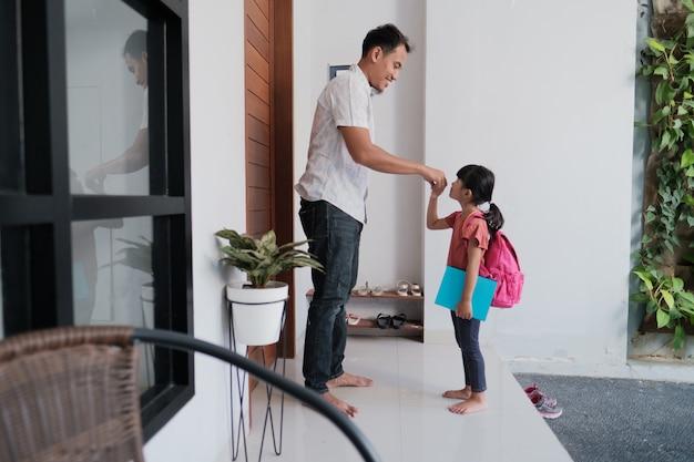 Ritratto di studentessa indonesiana della scuola primaria scuotere e baciare la mano di suo padre prima di andare a scuola Foto Premium