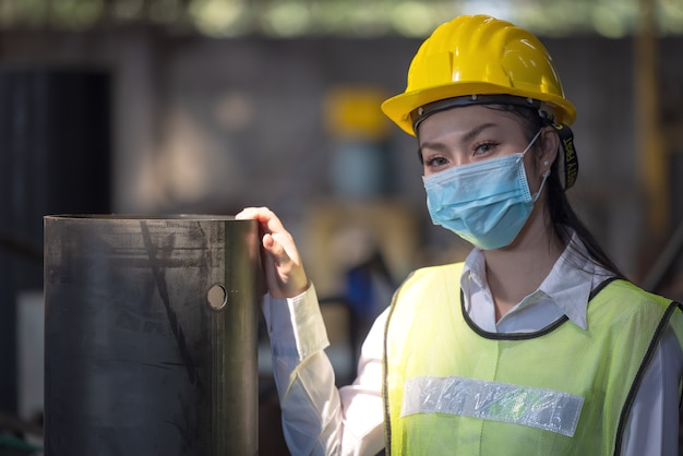 Un ritratto di un ingegnere industriale donna con maschera in piedi in una fabbrica.