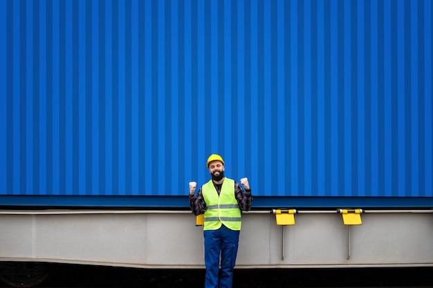Ritratto di lavoratore industriale in piedi dalla spedizione di container.