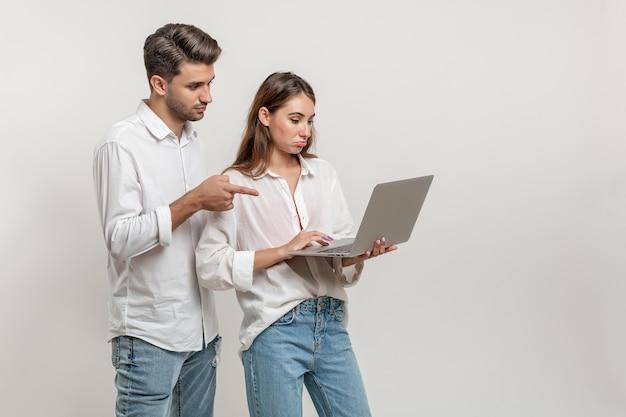 Ritratto di una coppia ispirata che utilizza il laptop per navigare nei siti di social network che puntano sullo schermo