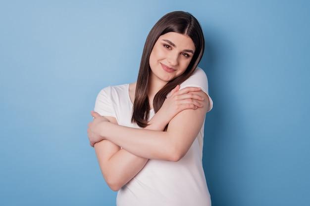 Il ritratto di una ragazza ispirata, adorabile e positiva, si abbraccia con le mani su sfondo blu