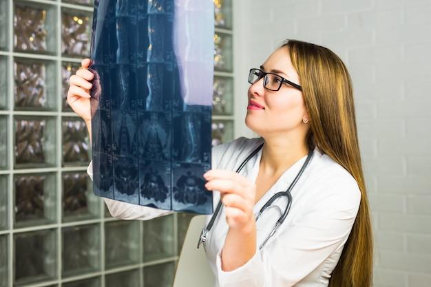 Ritratto del personale sanitario della donna intellettuale con camice bianco, guardando l'immagine radiografica dei raggi x su tutto il corpo