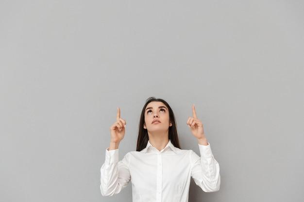 Ritratto di donna ufficio intelligente con lunghi capelli castani in camicia bianca guardando verso l'alto e puntando le dita su copyspace, isolato sopra il muro grigio