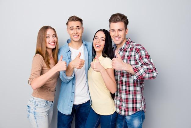 Ritratto di giovani intelligenti su grigio mostra i pollici in su