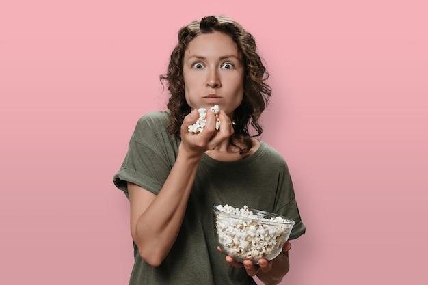 Ritratto di giovane donna interessata con i capelli ricci che mangia popcorn, esagerata con film o programmi tv.