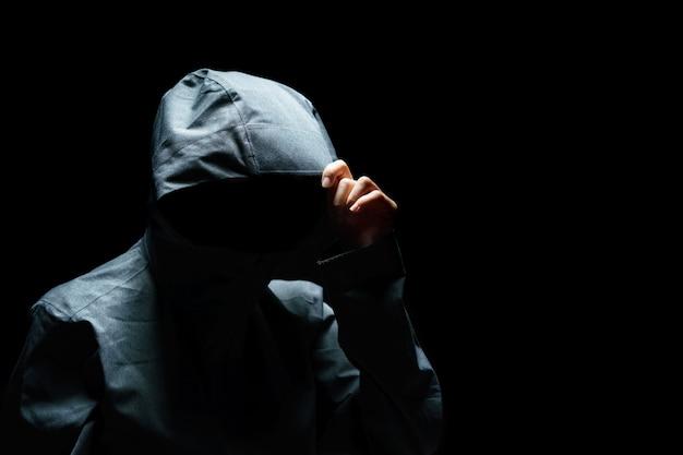 Ritratto di uomo invisibile nella cappa su sfondo nero.