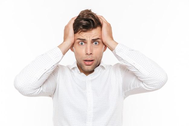 Ritratto dell'uomo deluso irritato che afferra la sua testa ed esprimendo problema.
