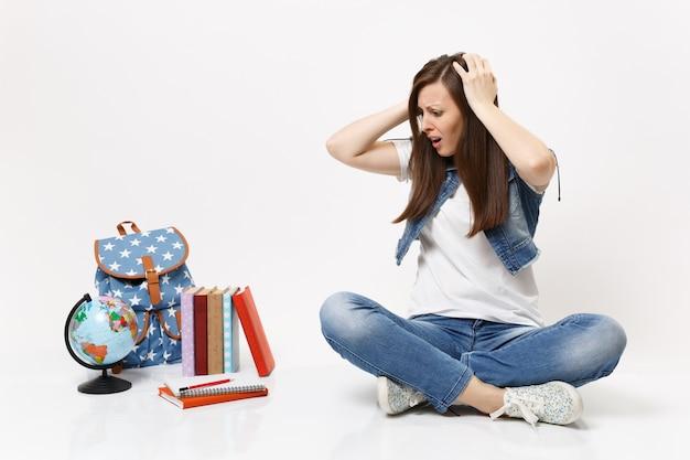 Ritratto di studentessa irritata insoddisfatta aggrappata alla testa guardando in basso e seduta vicino al globo, zaino, libri di scuola isolati sul muro bianco