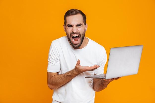Ritratto dell'uomo irritato 30s in maglietta bianca che grida e che tiene computer portatile d'argento, isolato
