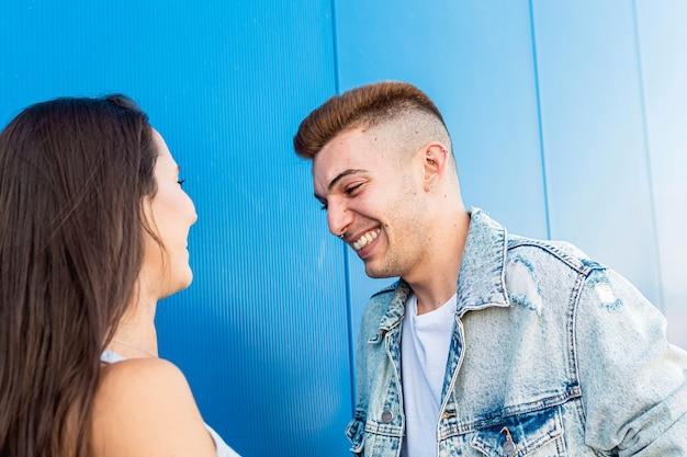 Ritratto di un giovane bello isolato che ride alla sua amica in blu
