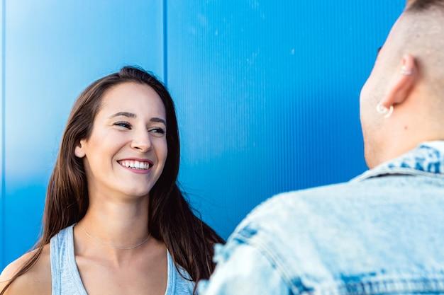Ritratto di una bella giovane donna isolata che sorride al suo ragazzo in blu