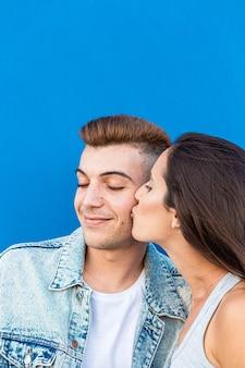 Ritratto di una giovane coppia isolata nell'amore che bacia in blu