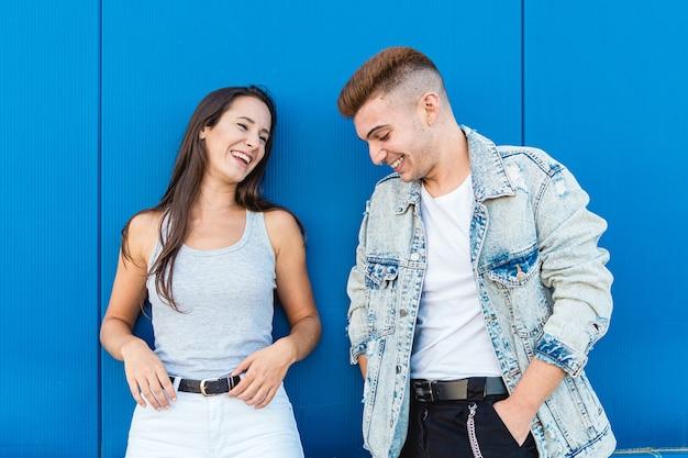 Ritratto di una giovane coppia isolata nell'amore che ride in blu