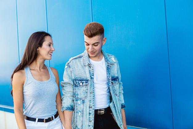Ritratto di una giovane coppia isolata nell'amore che sorride e che parla in blu