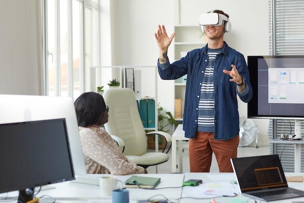 Ritratto del team di sviluppo it che progetta software di realtà immersiva con particolare attenzione all'uomo che indossa l'auricolare vr in ufficio, copia spazio