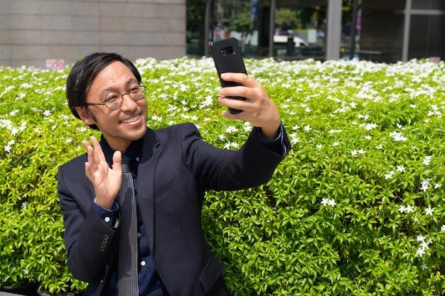Ritratto di uomo d'affari giapponese che ottiene aria fresca con la natura in città