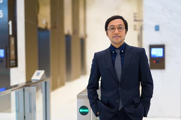 Ritratto di uomo d'affari giapponese nella hall della reception dell'edificio per uffici