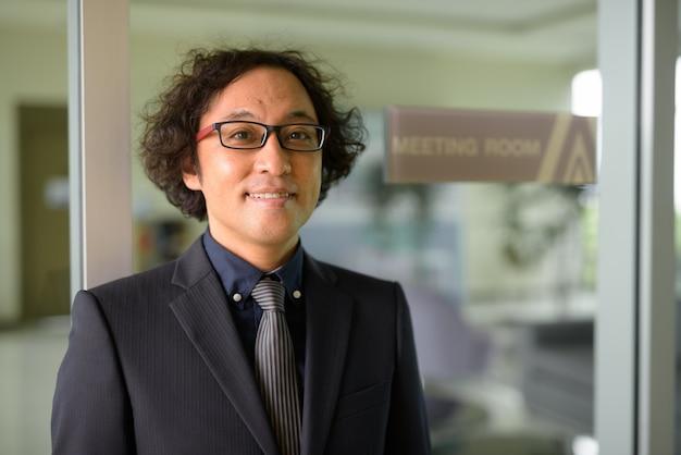 Ritratto di uomo d'affari giapponese con capelli ricci che indossa tuta in sala riunioni nell'edificio per uffici