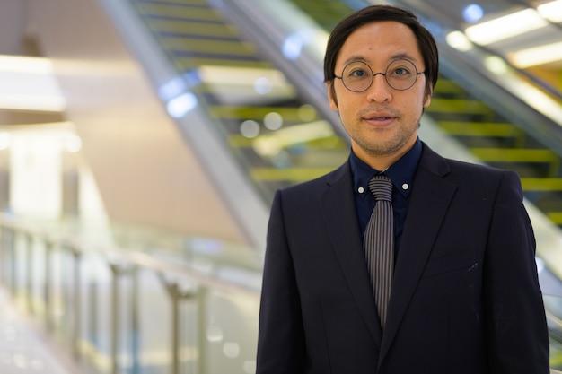 Ritratto di uomo d'affari giapponese che lavora all'interno dell'edificio per uffici Foto Premium