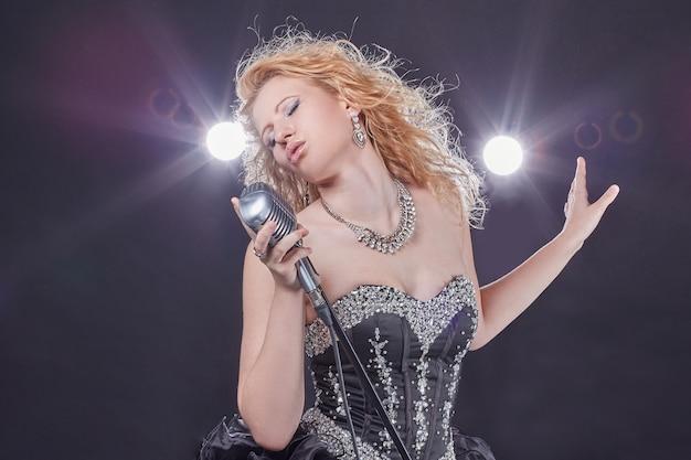 Ritratto di una ragazza cantante jazz isolata su uno sfondo scuro