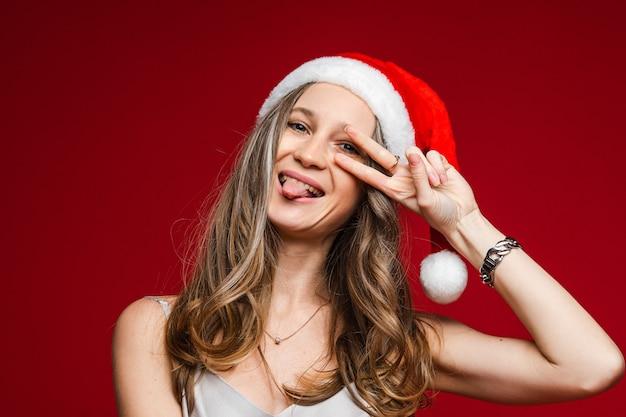 Ritratto di gioviale ragazza spensierata con capelli biondi ondulati che indossa un cappello rosso da babbo natale con bordo bianco che mostra il segno di pace con le dita sugli occhi e con la lingua fuori