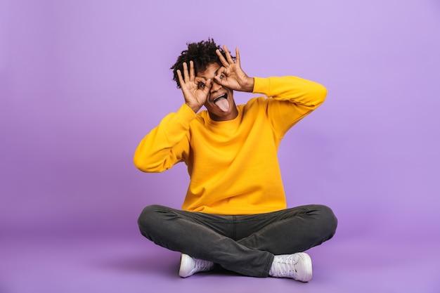 Ritratto di gioioso ragazzo afroamericano seduto sul pavimento con le gambe incrociate e ti guarda attraverso il binocolo facendo con le dita, isolato su sfondo viola