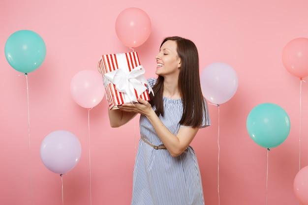 Ritratto di gioiosa donna attraente in abito blu guardando scatola rossa con regalo presente su sfondo rosa pastello con mongolfiere colorate. festa di compleanno, concetto di emozioni sincere della gente.