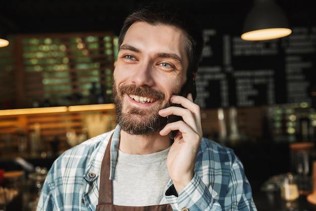 Ritratto di gioioso barista che indossa un grembiule che sorride e parla al cellulare in un caffè di strada o in un caffè all'aperto