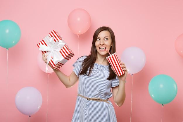 Ritratto di gioiosa bella donna in abito blu che tiene scatola rossa con regalo presente bevendo soda o cola da un bicchiere di plastica su sfondo rosa pastello con mongolfiere colorate. festa di compleanno.