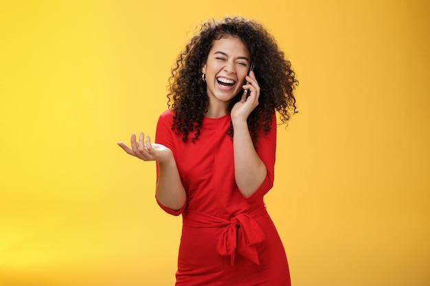 Ritratto di gioiosa affascinante femmina europea in abito rosso con i capelli ricci che ride ad alta voce mentre spettegola con un amico tramite smartphone chiudi gli occhi mentre ridacchia gesticolando, ascoltando uno scherzo tramite il telefono cellulare.
