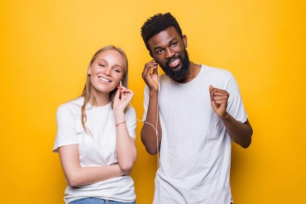 Ritratto di coppia gioiosa che canta mentre si utilizza smartphone e auricolari insieme isolati su un muro giallo