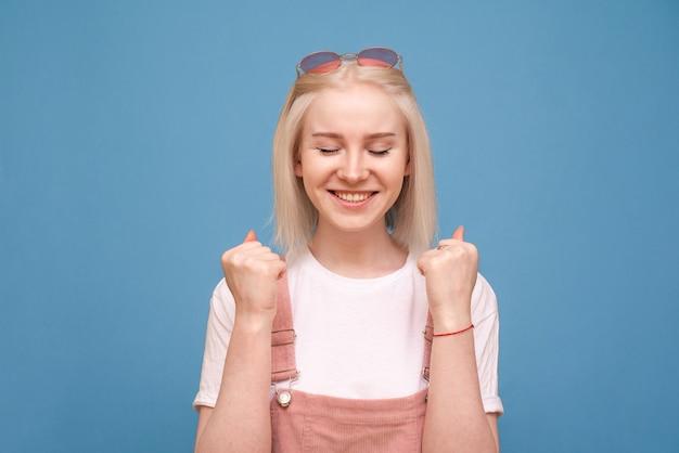 Ritratto di una ragazza allegra che tiene i suoi pugni, felice con gli occhi chiusi