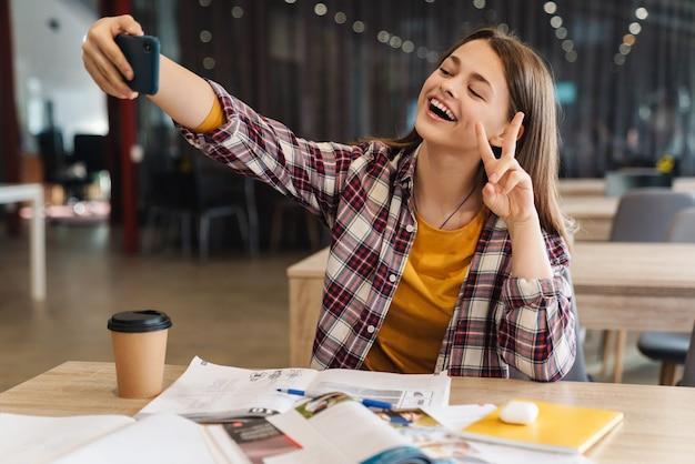 Ritratto di una ragazza gioiosa che si fa selfie sul cellulare e fa un gesto di pace mentre fa i compiti nella biblioteca del college