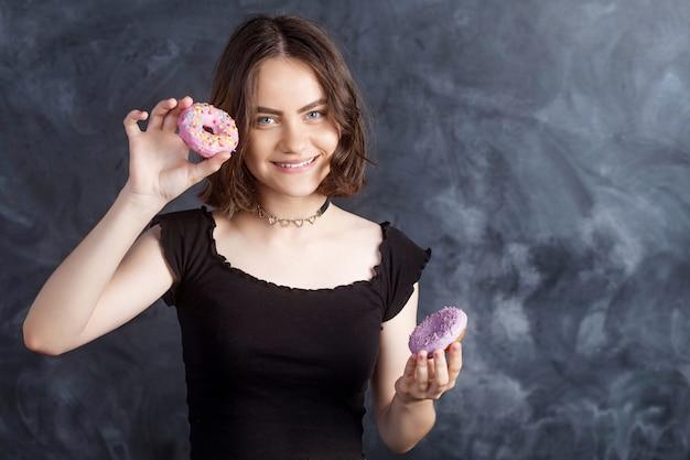 Ritratto di ragazza allegra con ciambelle sul muro nero. ragazza felice che tiene ciambelle fresche e sorridente. buon umore, concetto di dieta.