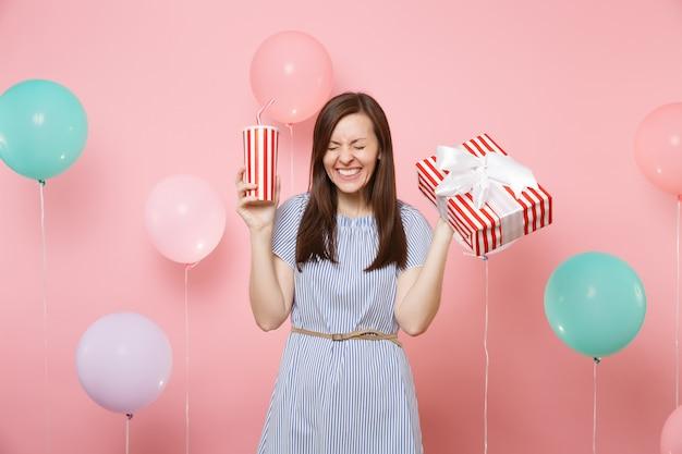 Ritratto di gioiosa donna felice con gli occhi chiusi in abito blu che tiene scatola rossa con regalo regalo e tazza di plastica di soda o cola su sfondo rosa con mongolfiere colorate. festa di compleanno.