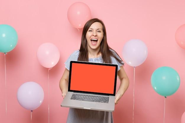 Ritratto di gioiosa donna felice con la bocca aperta in abito blu che tiene in mano un computer pc portatile con schermo vuoto vuoto su sfondo rosa pastello con mongolfiere colorate. concetto di festa di compleanno.