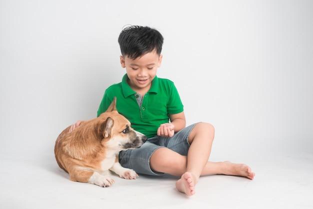 Ritratto di un ragazzino gioioso divertendosi con il cane corgi gallese sul pavimento