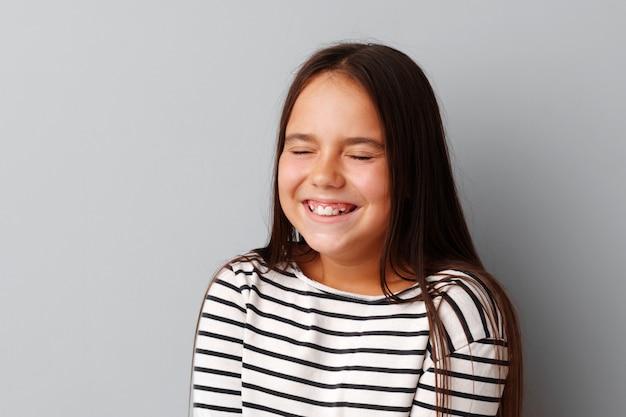 Ritratto della bambina allegra che ride sopra un fondo grigio
