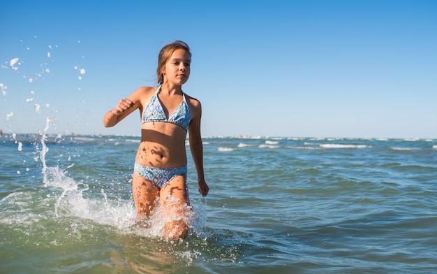 Ritratto di una gioiosa bambina positiva nuotare nel mare in una soleggiata giornata estiva calda