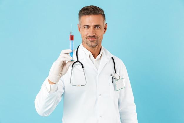 Ritratto di gioioso medico con lo stetoscopio in guanti che tengono la siringa, in piedi isolato sopra la parete blu