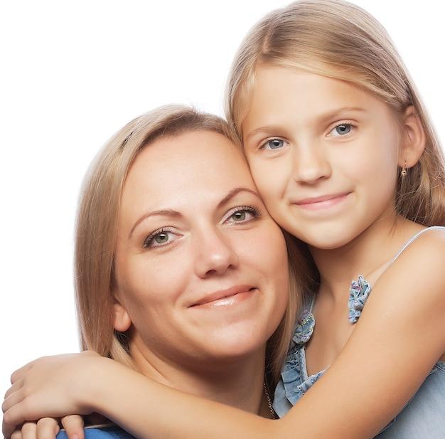Ritratto di una madre gioiosa e di sua figlia che sorridono alla telecamera
