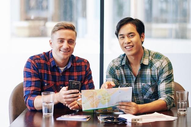 Ritratto di gioiosi amici multietnici seduti al tavolino del bar e discutendo la mappa della città in cui viaggeranno